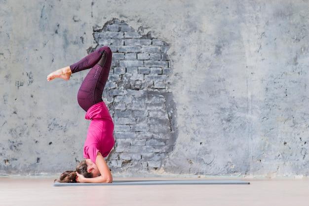 Vista laterale di una giovane donna fitness in piedi sulla sua testa facendo yoga Foto Gratuite