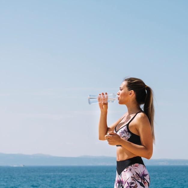 Vista laterale di una giovane donna in piedi davanti al mare acqua potabile dalla bottiglia Foto Gratuite