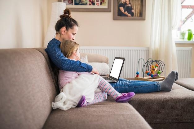 Vista laterale di una madre che si siede con sua figlia che per mezzo del computer portatile Foto Gratuite