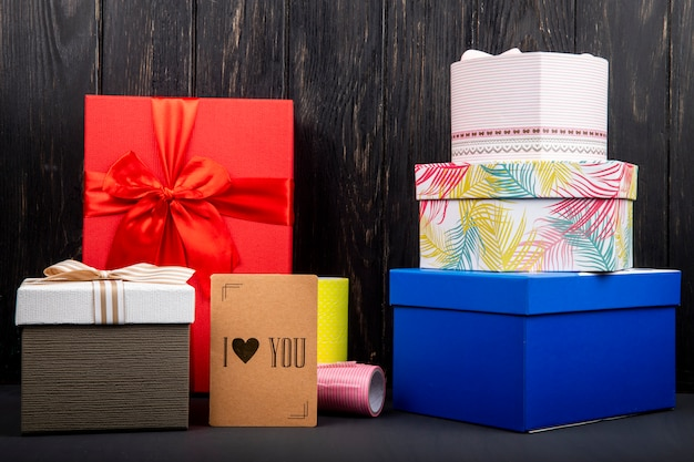Vista laterale di una pila di scatole colorate presenti e un piccolo ti amo carta al tavolo di legno scuro Foto Gratuite