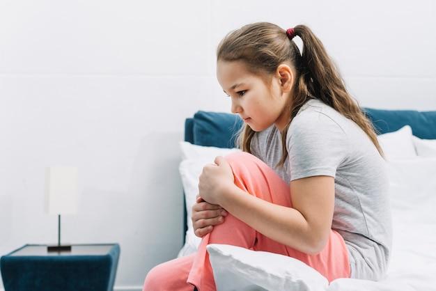 Vista laterale di una ragazza che ha dolore nel suo ginocchio che si siede sul letto a casa Foto Gratuite