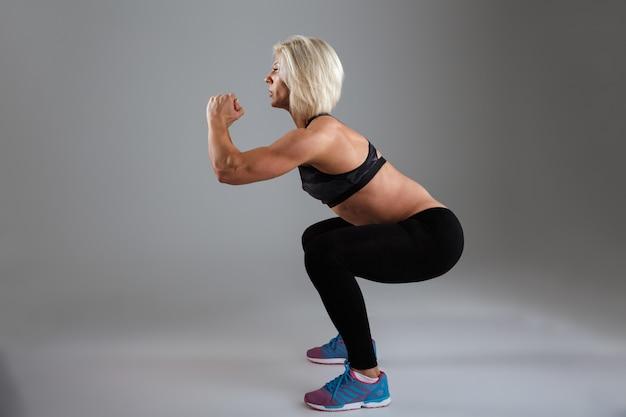 Vista laterale di una sportiva adulta muscolare concentrata Foto Gratuite