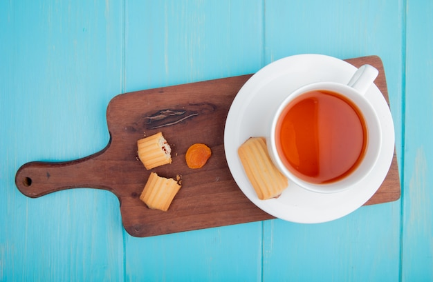 Vista laterale di una tazza di tè con i biscotti e l'albicocca secca sul tagliere di legno sul blu Foto Gratuite