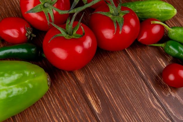 Vista laterale di verdure fresche pomodori maturi cetrioli peperoncino e peperoni colorati sul tavolo di legno rustico Foto Gratuite
