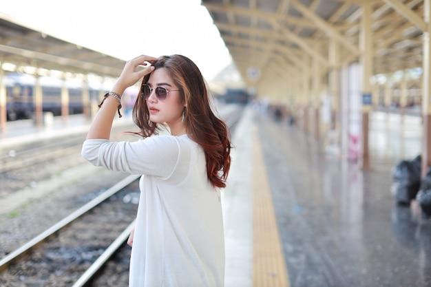 Vista laterale giovane donna asiatica in piedi e in posa nella stazione ferroviaria con la faccia di bellezza e sorridente Foto Premium