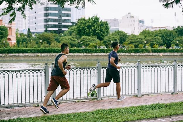 Vista laterale integrale di due ragazzi che pareggiano al fiume sul ponte Foto Gratuite