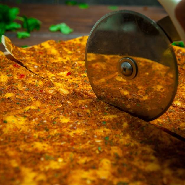 Vista laterale lahmacun con coltello da taglio per pizza e prezzemolo Foto Gratuite