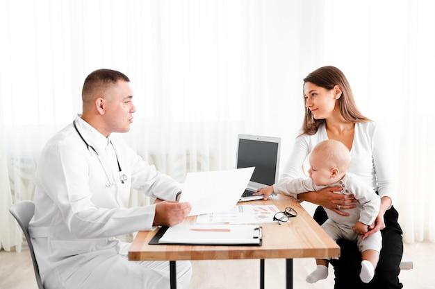 Vista laterale medico consulenza bambino appena nato Foto Gratuite