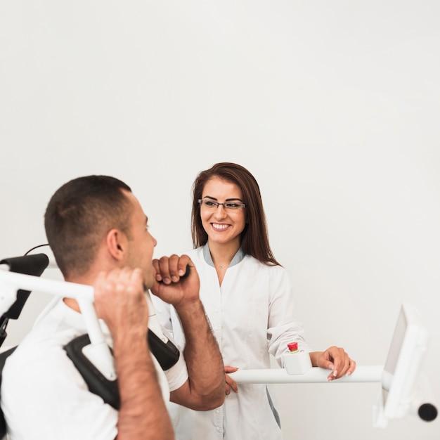 Vista laterale paziente facendo esercizi supervisionati dal medico Foto Gratuite