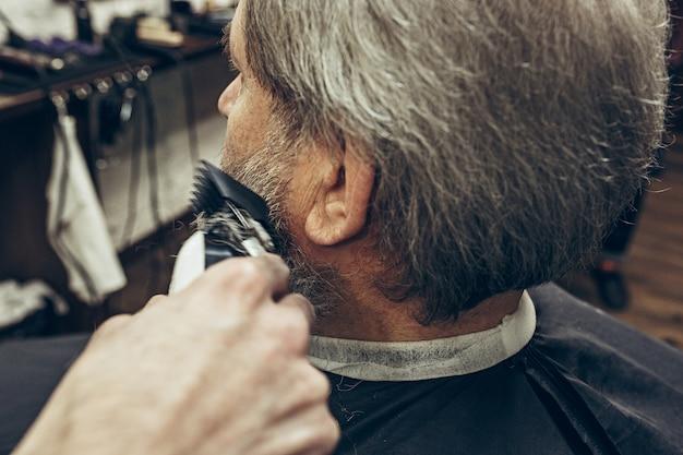 Vista laterale posteriore del primo piano uomo caucasico barbuto senior bello che ottiene governare barba nel barbiere moderno. Foto Gratuite