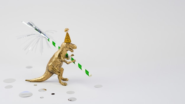 Vista laterale t-rex dorato con cappello compleanno Foto Gratuite