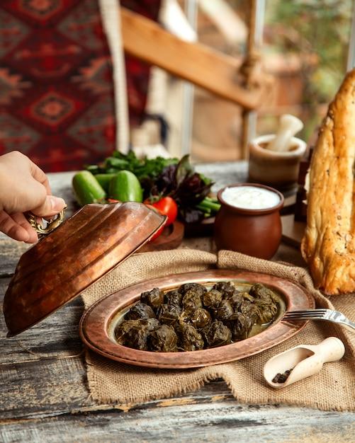 Vista laterale un dolma azero tradizionale della carne del piatto dalle foglie dell'uva con yogurt e le verdure Foto Gratuite