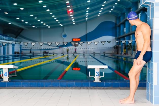Vista laterale uomo atletico guardando la piscina Foto Gratuite