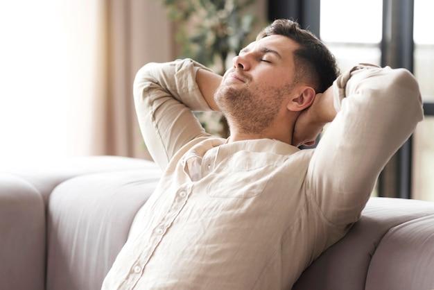Vista laterale uomo rilassante sul divano Foto Gratuite