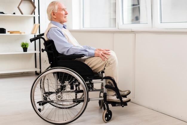 Vista laterale vecchio seduto sulla sedia a rotelle Foto Gratuite