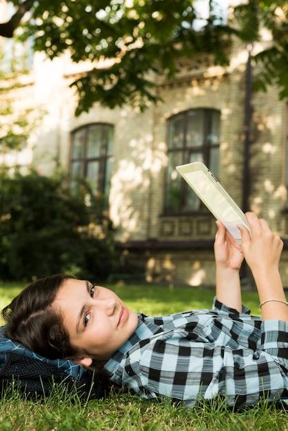 Vista laterale vicino di scuola ragazza utilizzando la tavoletta Foto Gratuite
