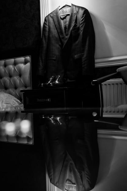 Vista monocromatica dell'abito da sposa per uno sposo che riflette sul tavolo di vetro Foto Gratuite