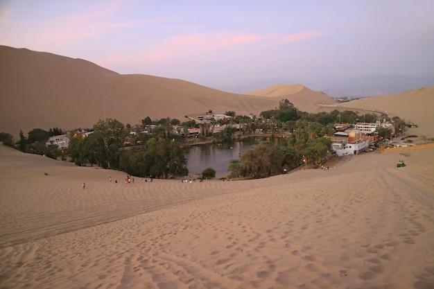 Vista mozzafiato di huacachina, la città oasi vista dalla duna di sabbia al tramonto, ica, perù Foto Premium