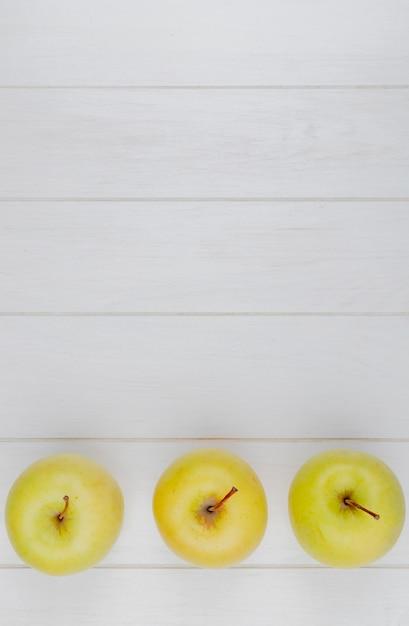 Vista orizzontale delle mele verdi su superficie di legno con lo spazio della copia Foto Gratuite