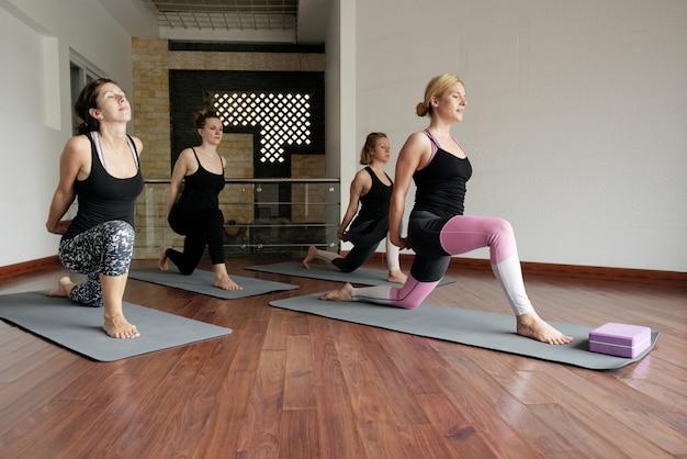 Vista panoramica della lezione di fitness piena di donne che fanno yoga Foto Gratuite