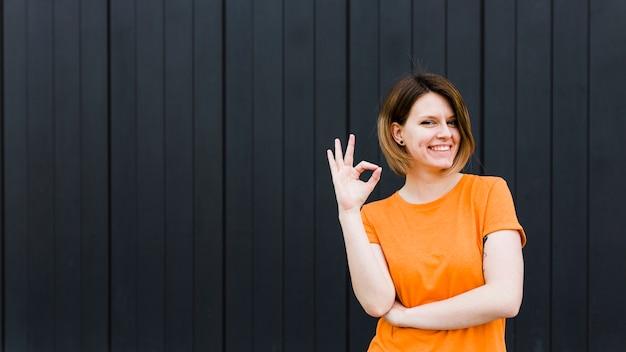 Vista panoramica di un ritratto sorridente di una giovane donna che mostra segno giusto Foto Gratuite