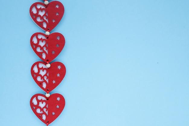 Vista piana di cuori di san valentino su sfondo blu. simbolo di amore e concetto di san valentino. copyplace, spazio per testo e logo. Foto Premium