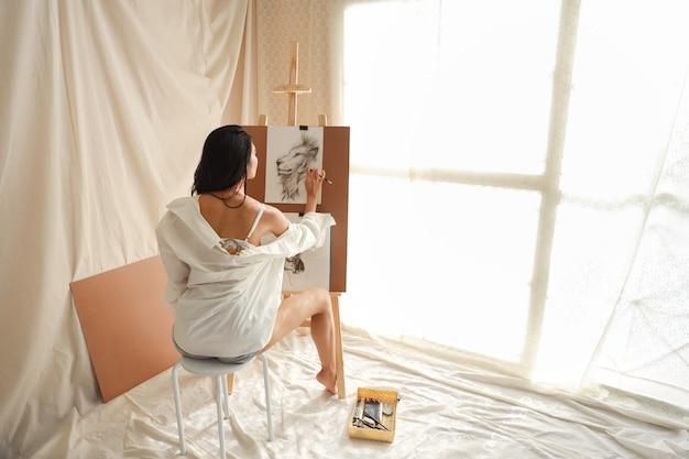 Vista posteriore artista donna in camicia bianca disegno foto con la matita (concetto di stile di vita della donna) Foto Premium