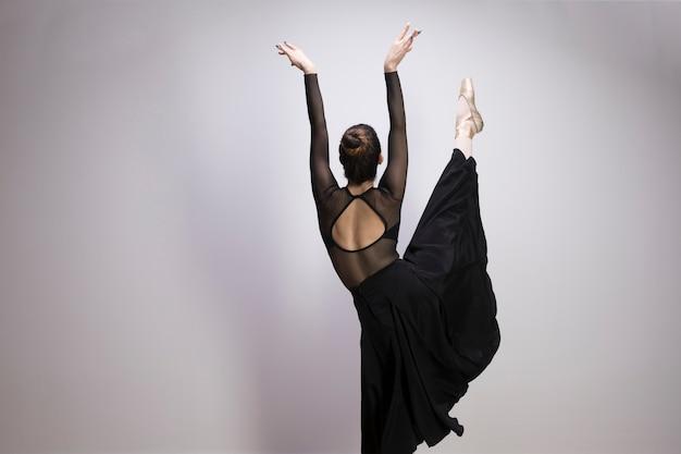 Vista posteriore ballerina con una gamba in alto Foto Gratuite