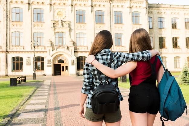 Vista posteriore colpo medio di due ragazze adolescenti che abbraccia Foto Gratuite