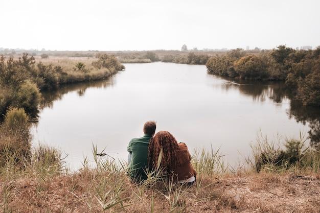 Vista posteriore coppia seduta accanto a uno stagno Foto Gratuite