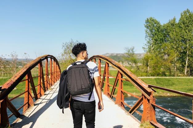 Vista posteriore del giovane che cammina sul ponte sul bellissimo fiume Foto Gratuite