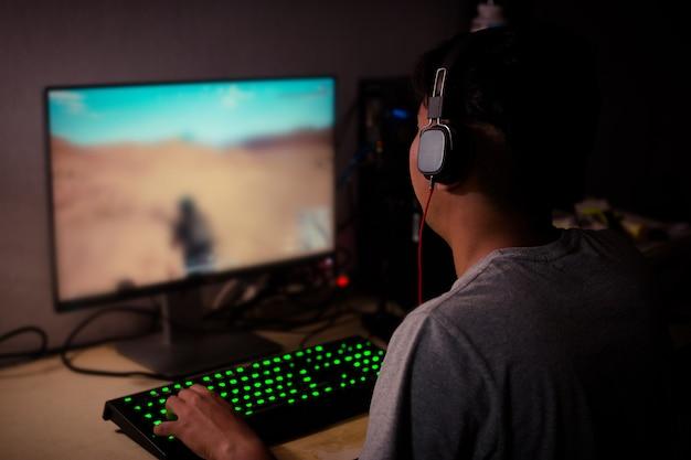 Vista posteriore del giovane giocatore che gioca con i videogiochi a casa Foto Premium
