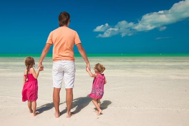 Vista posteriore del giovane padre e le sue due adorabili figlie in una vacanza esotica Foto Premium