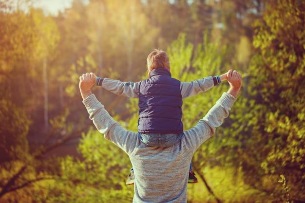 Vista posteriore del padre suo figlio sulle spalle sulla natura. Foto Premium