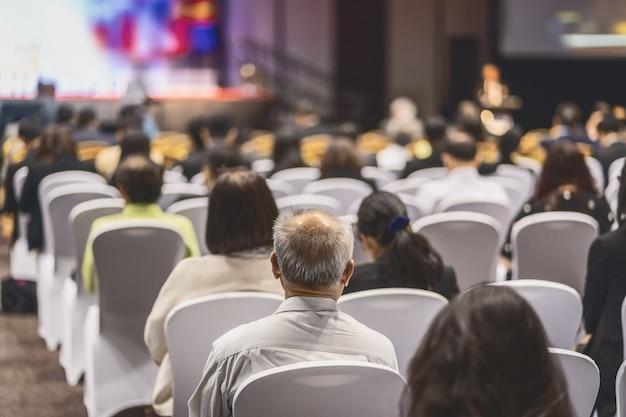 Vista posteriore del pubblico che ascolta relatori sul palco nella sala conferenze o nella riunione del seminario Foto Premium