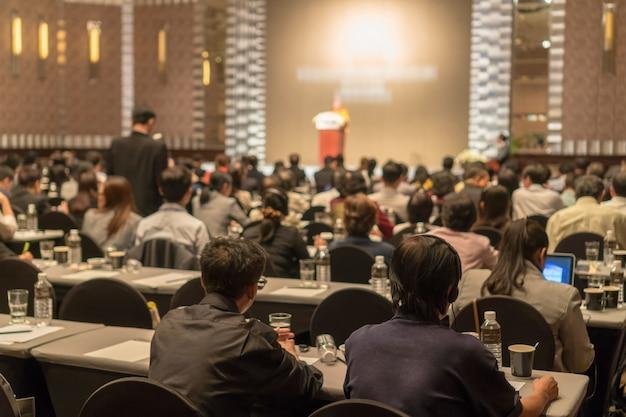Vista posteriore del pubblico che indossa e ascolta gli altoparlanti via interpreter headset sul palco Foto Premium