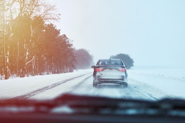 Vista posteriore dell'automobile sulla strada di inverno nevoso Foto Premium