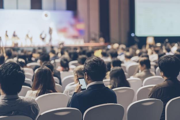 Vista posteriore dell'udienza del pubblico altoparlanti sul palco nella sala delle conferenze o nella riunione del seminario Foto Premium