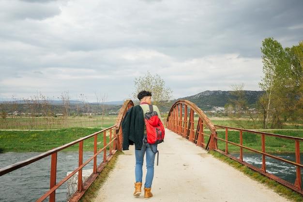 Vista posteriore dell'uomo che cammina sul ponte sul fiume Foto Gratuite