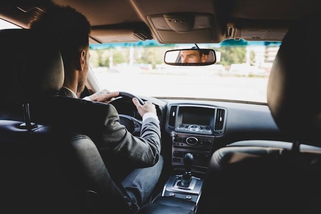 Vista posteriore dell'uomo d'affari che guida l'auto Foto Gratuite