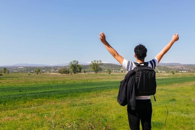 Vista posteriore dell'uomo in piedi vicino al bellissimo paesaggio verde con zaino Foto Gratuite