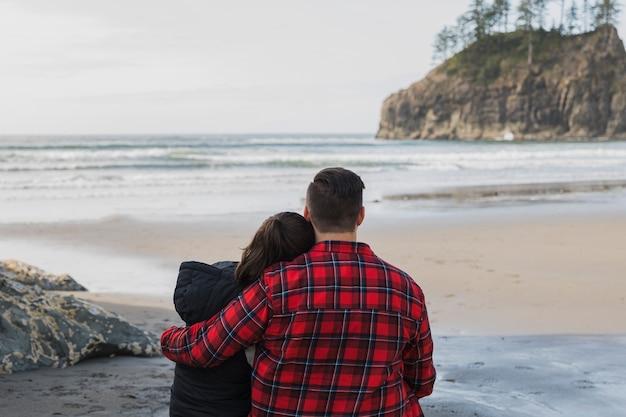Vista posteriore della coppia abbracciata sulla riva Foto Gratuite
