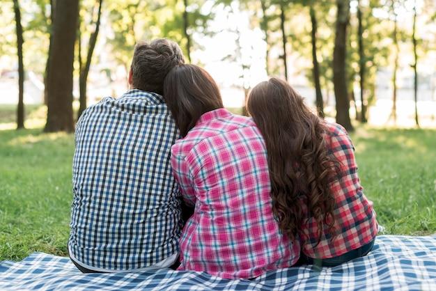 Vista posteriore della famiglia che si siede nel parco con appoggiato le loro teste sulle spalle degli altri Foto Gratuite