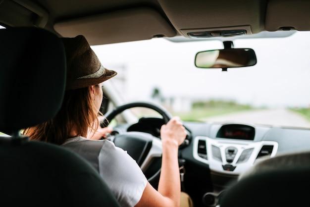 Vista posteriore della giovane donna alla guida di un'auto. Foto Premium