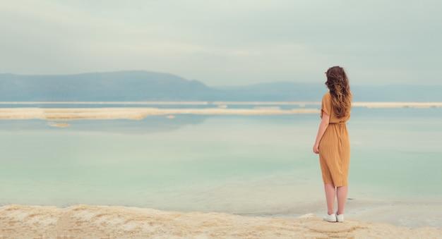 Vista posteriore della ragazza alla moda che porta vestito sulla spiaggia Foto Premium