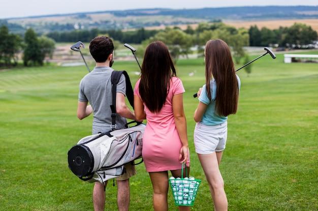 Vista posteriore di amici con attrezzatura da golf Foto Gratuite