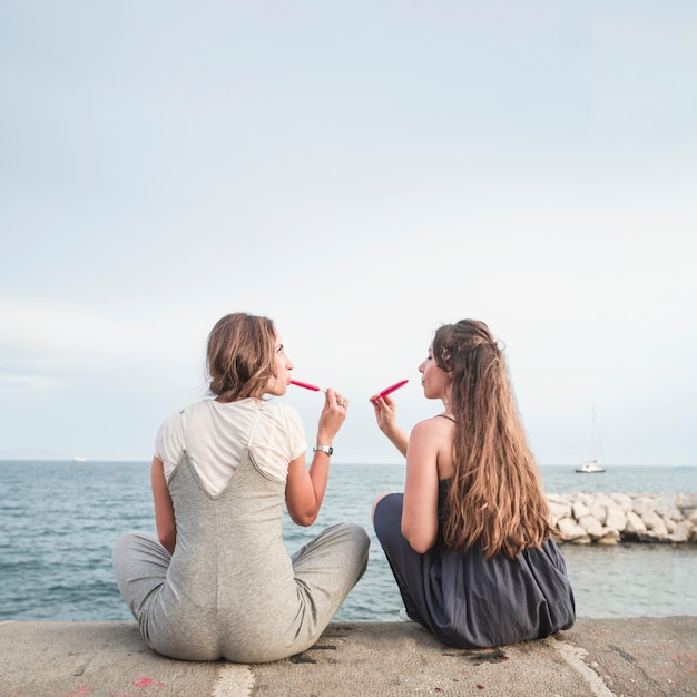Vista posteriore di due amici femminili seduti sul molo mangiare ghiaccioli rossi Foto Gratuite