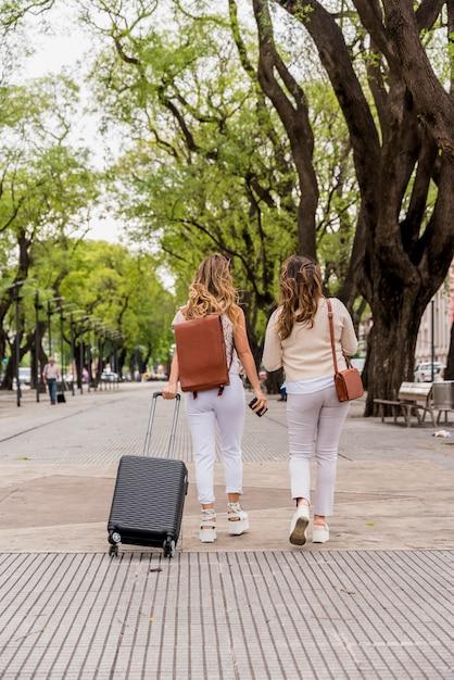 Vista posteriore di due giovani donne che camminano nel parco con borsa dei bagagli Foto Gratuite