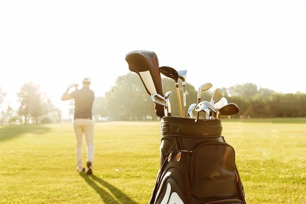 Vista posteriore di un club di golf d'oscillazione del giocatore di golf maschio Foto Gratuite