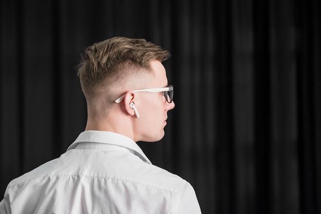 Vista posteriore di un giovane uomo che indossa occhiali da vista con auricolare wireless sul suo orecchio Foto Gratuite